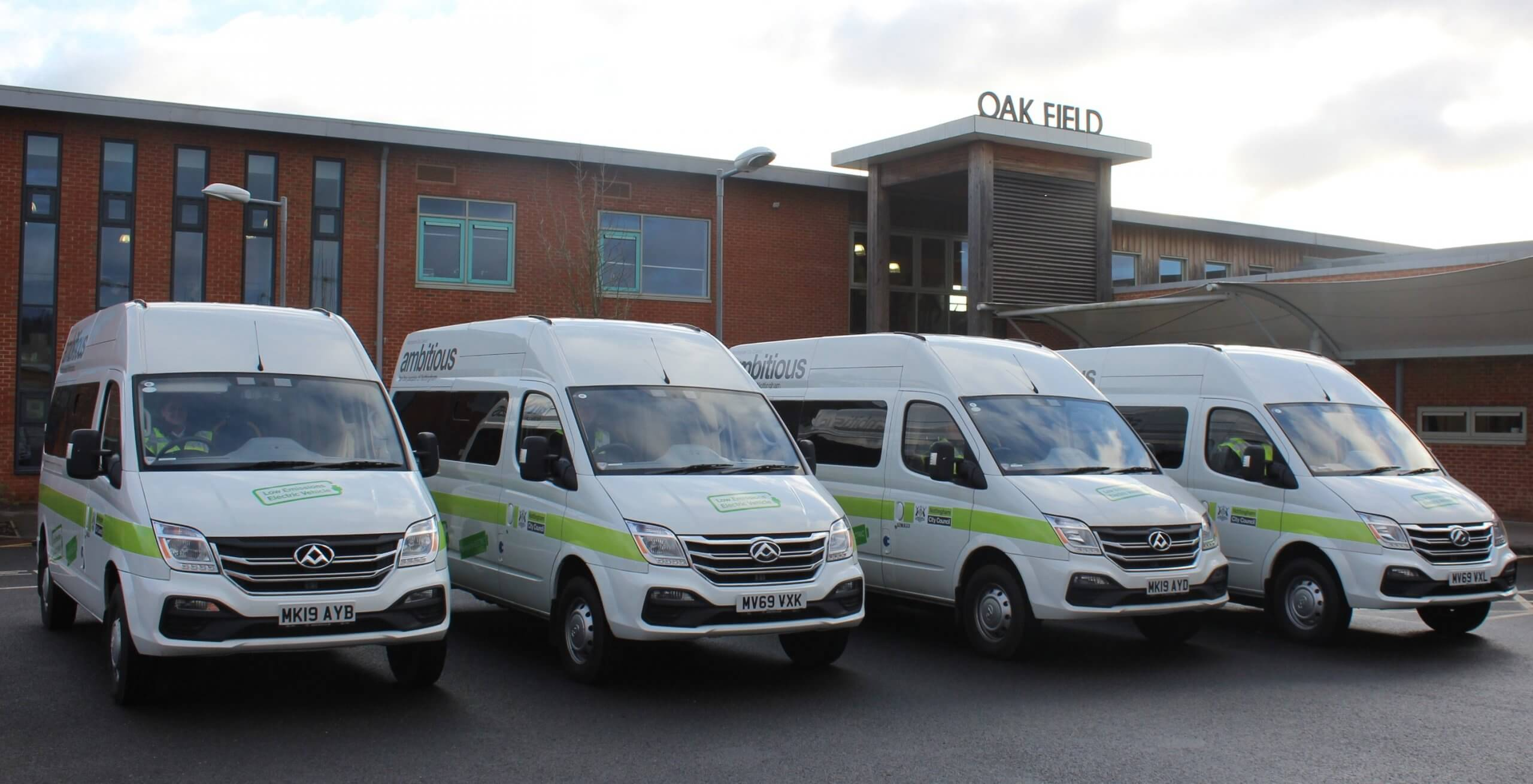 Four electric minibuses in front of Oakfield school