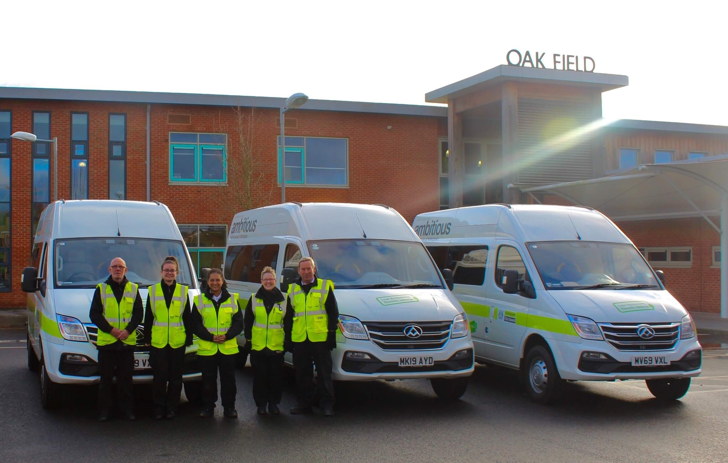Staff in front of electric minibuses at Oakfield school