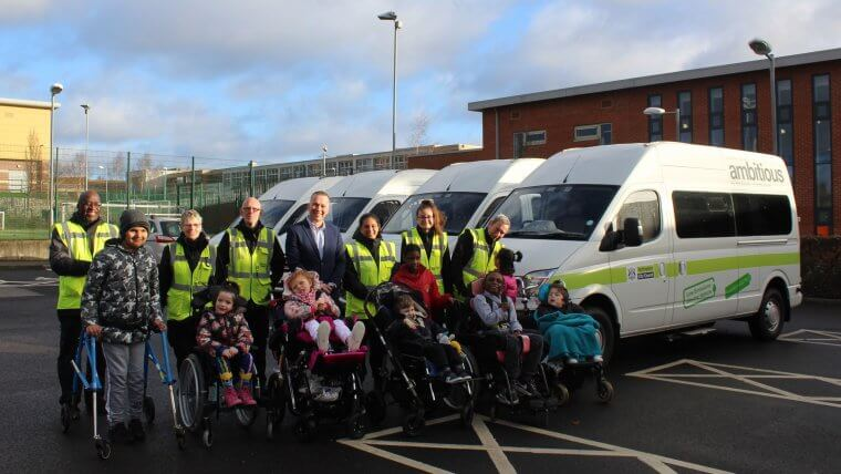 Children in front of new electric minibuses at Oakfield school