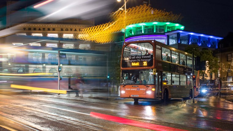 Buses at night outside the Corner House with blurred lights showing movement