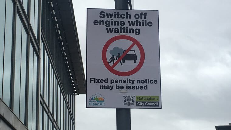 Road sign asking drivers to switch of engines while waiting