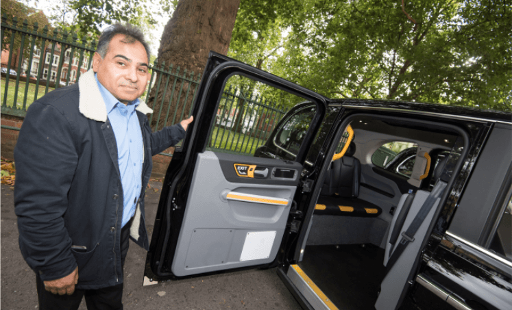 Khalid, taxi driver holding the door to his taxi open