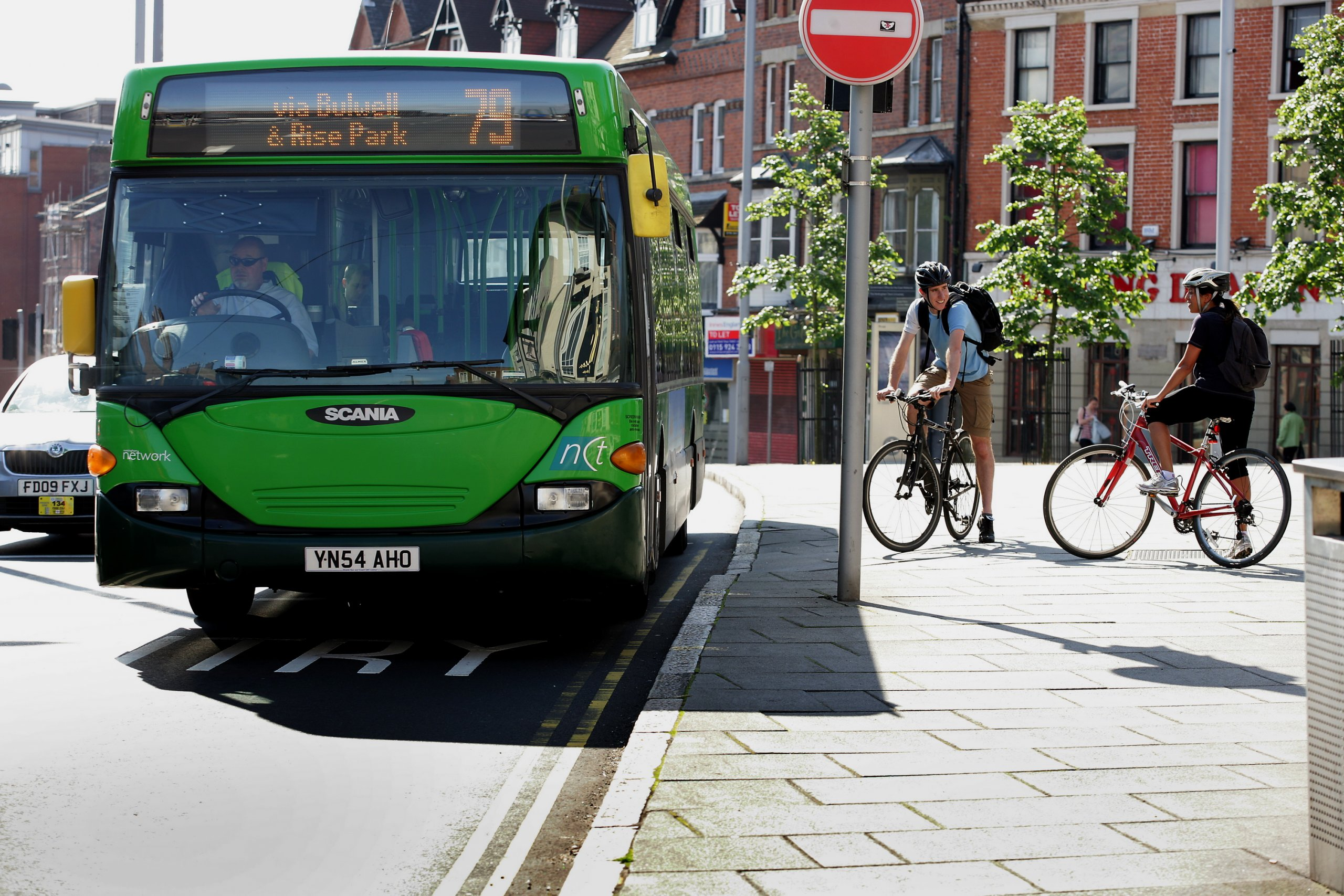Cyclists standing next to a bus
