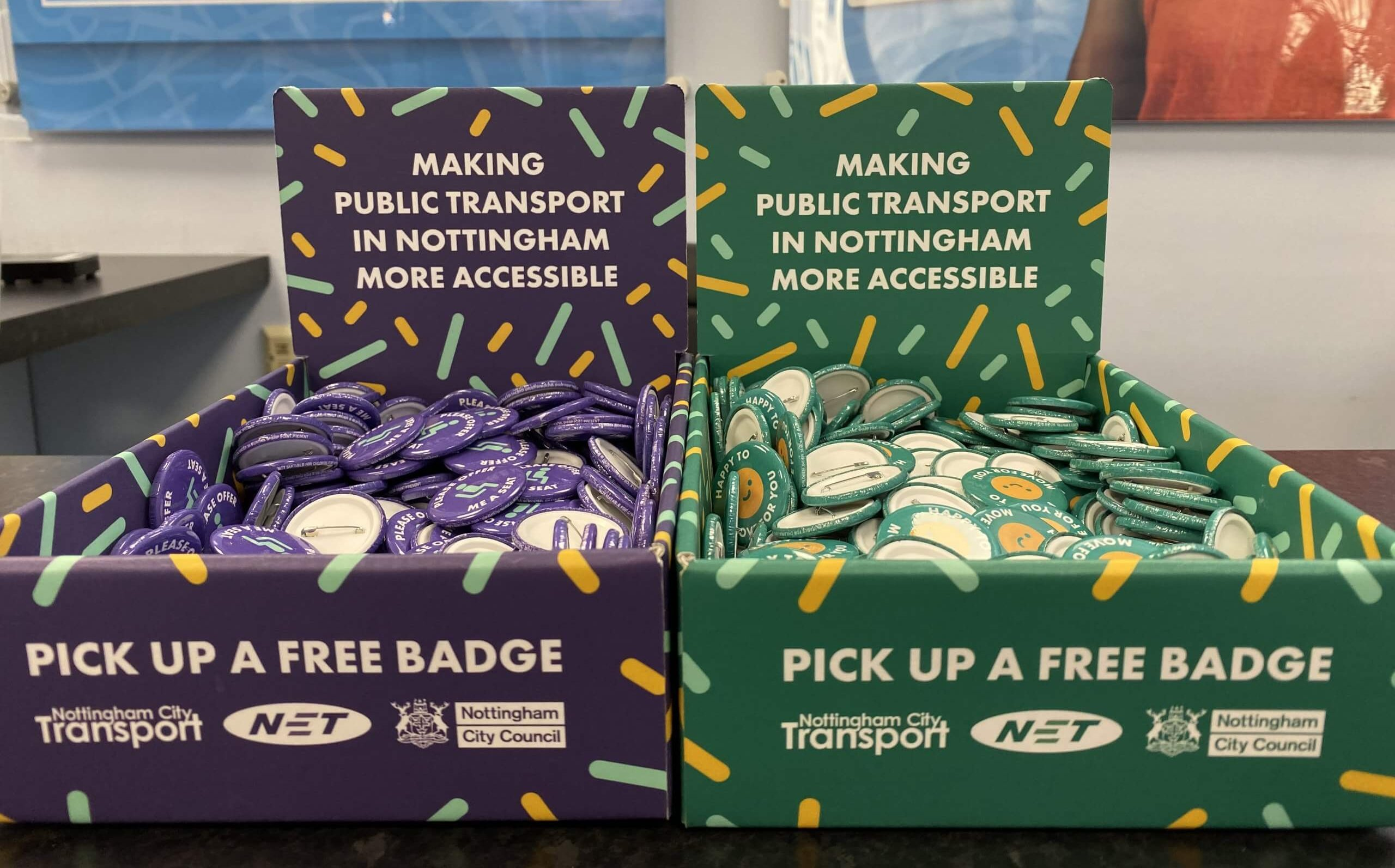 """Boxes of badges at NCT's travel centre for the """"please offer me a seat"""" campaign"""
