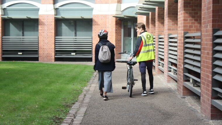 Zoe walking alongside a cycle-buddying mentor and bike