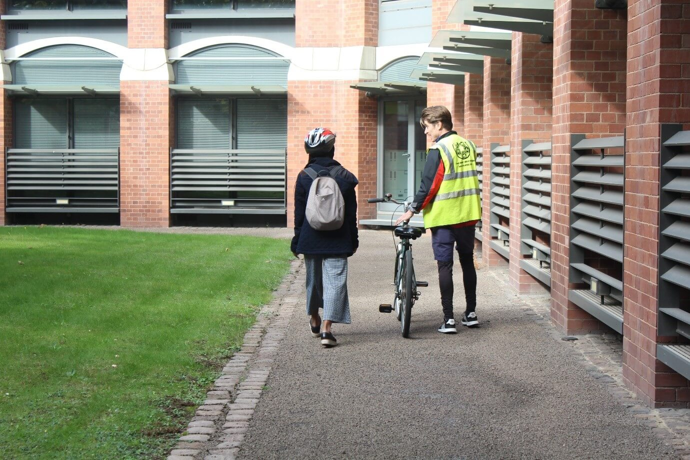 Zoe walking alongside a cycle-buddying mentor and bike