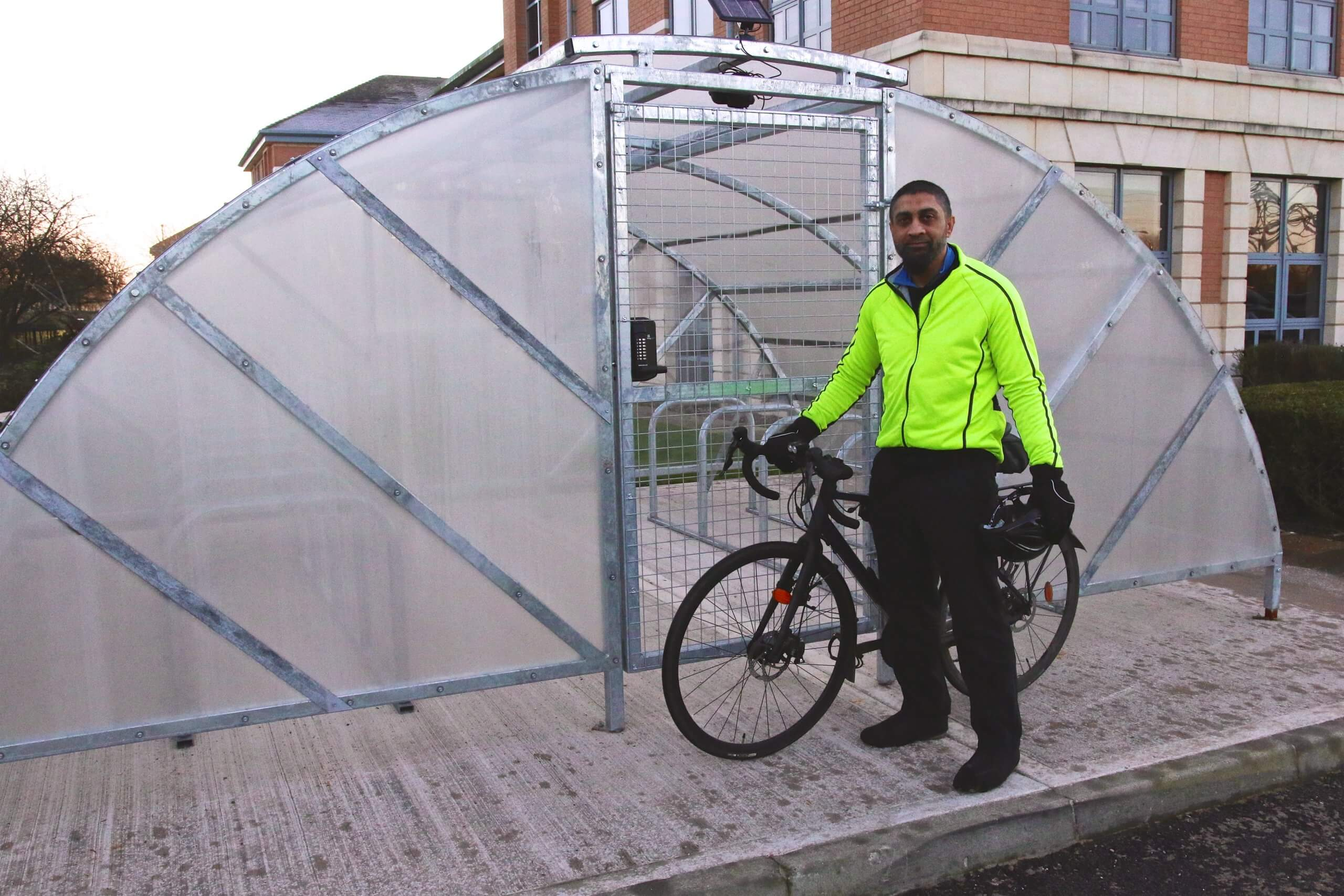 Experian Employee standing next to cycle shelter